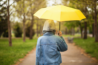 Person wearing a jean jacket and holding up a yellow umbrella walking down a path in the woods